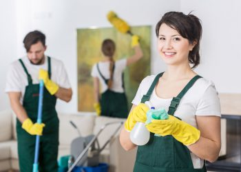 Group of young hard working professional cleaners in dirty apartment